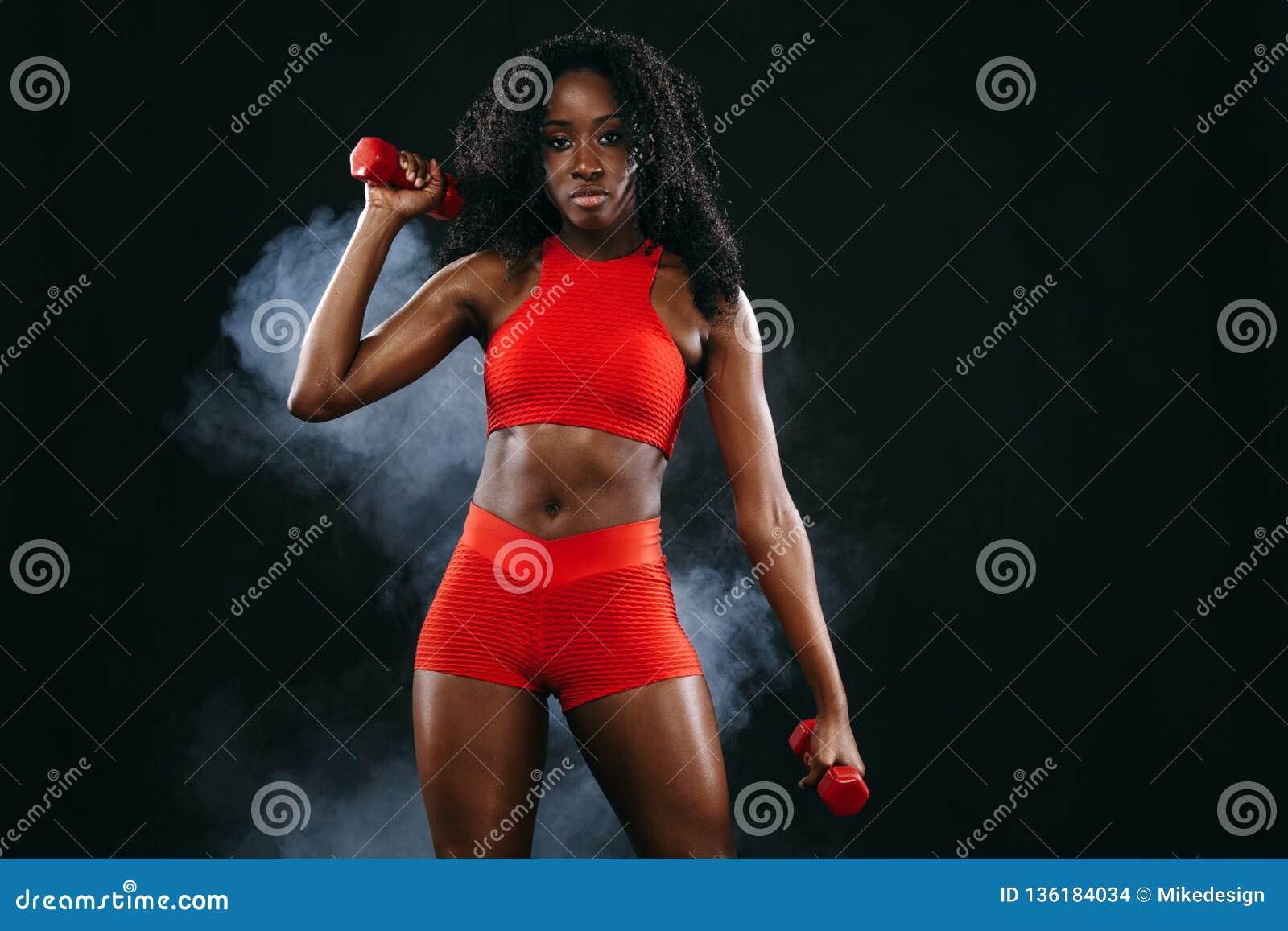 La femme noire convenable sportive de peau dans les vêtements de sport rouges, athlète avec des haltères fait la forme physique s