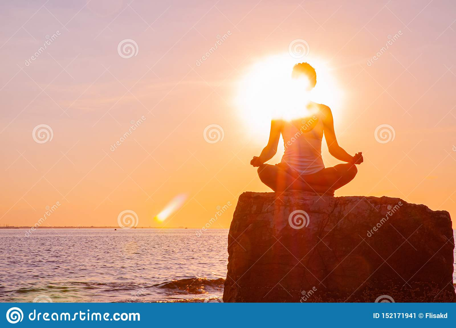La femme pratique le yoga se reposant sur la pierre dans la pose de Lotus au coucher du soleil Silhouette de femme m?ditant sur l