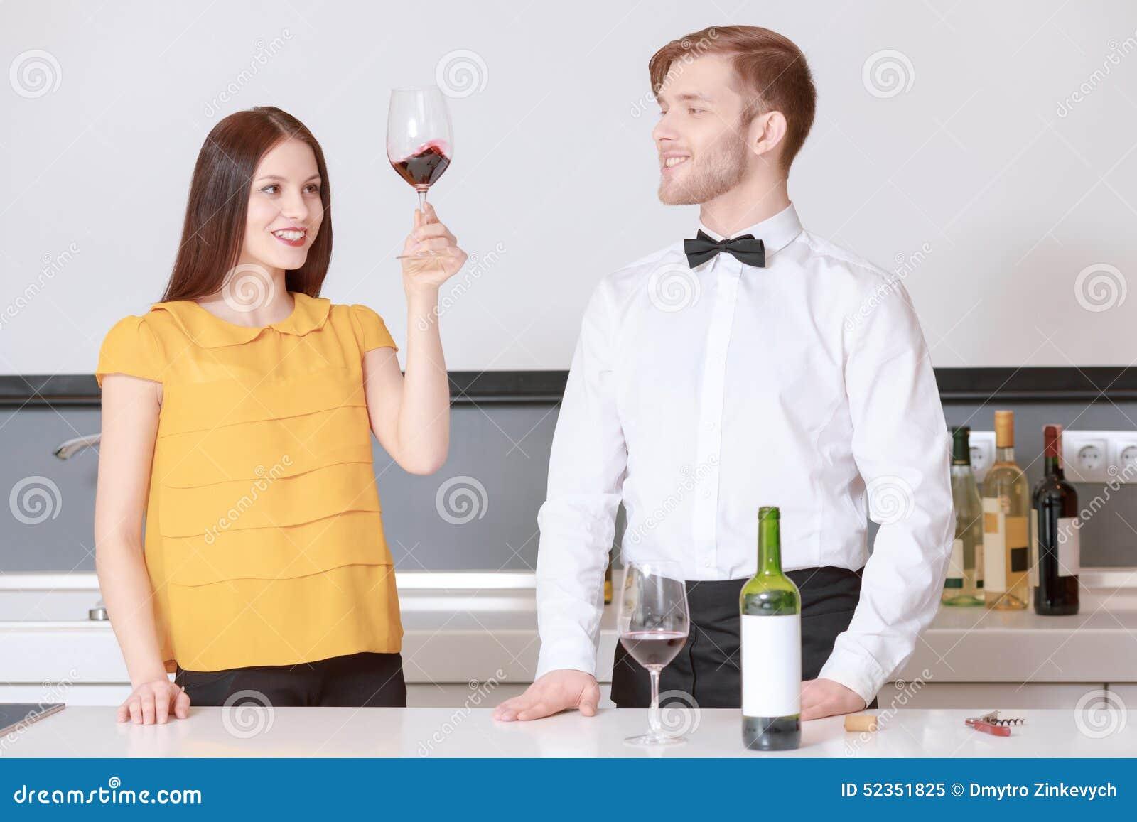 La femme regarde le vin en verre