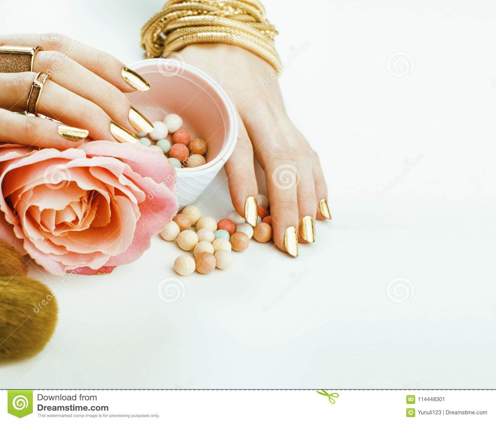 La femme remet avec la manucure d or beaucoup d anneaux tenant des brosses, compose la substance d artiste élégante et pure