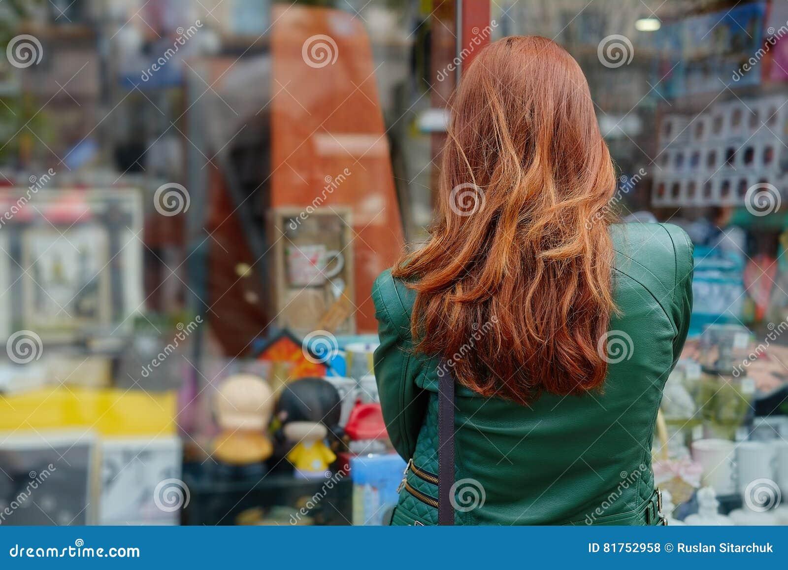 La femme rousse regarde une fenêtre de boutique