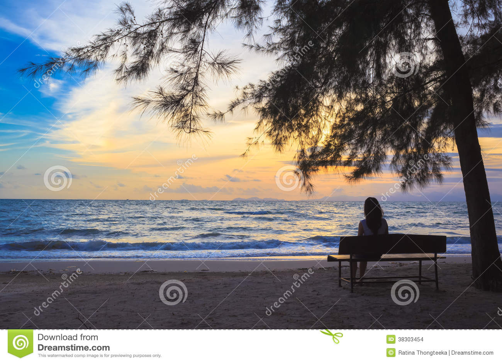 La femme s asseyent sur des chaises sous l arbre sur la plage