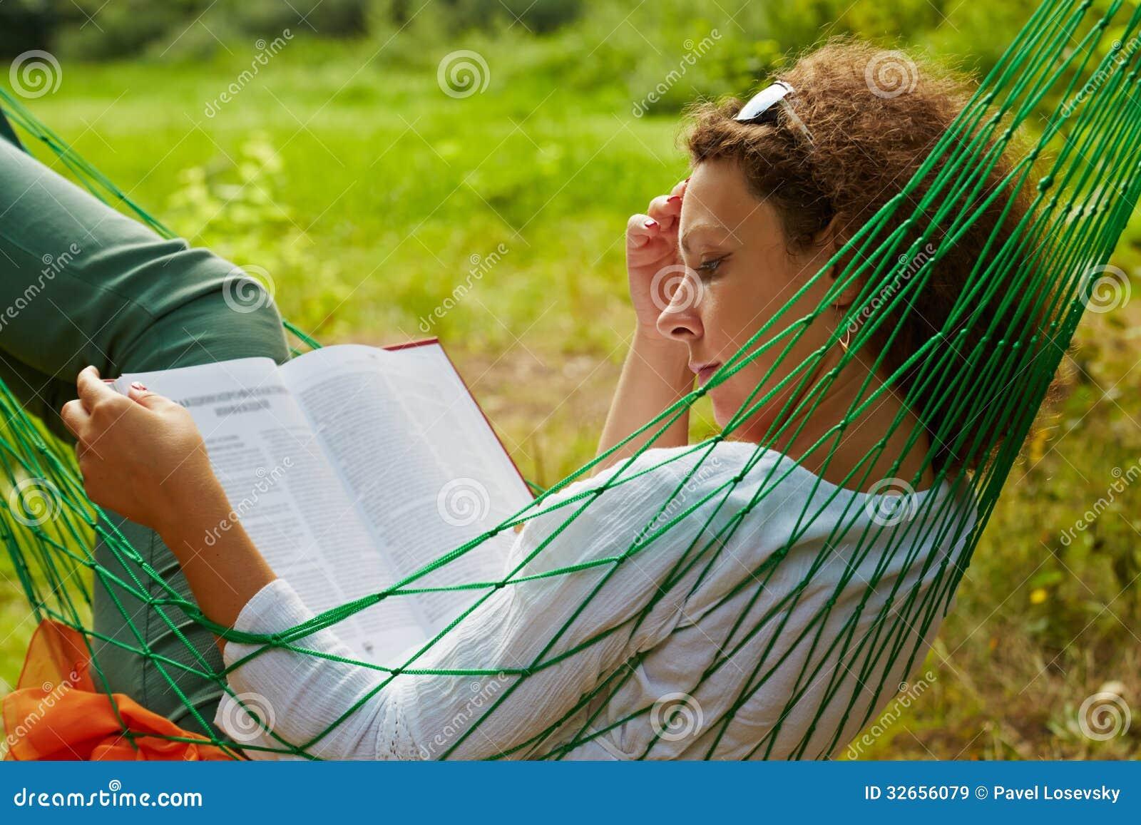 La femme se situe dans l hamac et lit le livre