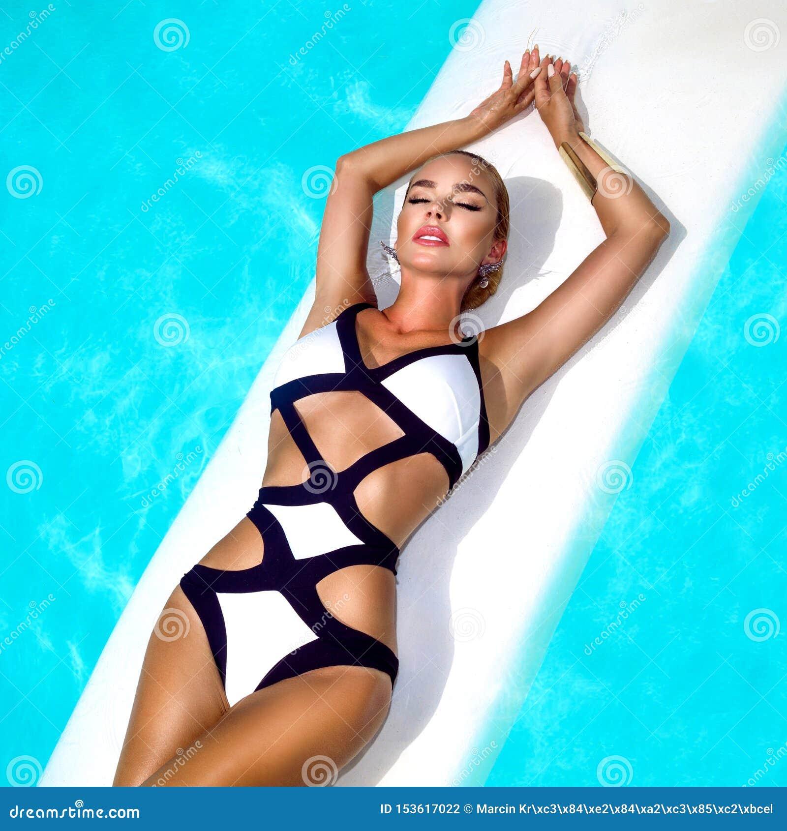 La femme sexy élégante dans le bikini noir et blanc sur le corps mince et bien fait bronzé pose près de la piscine - image