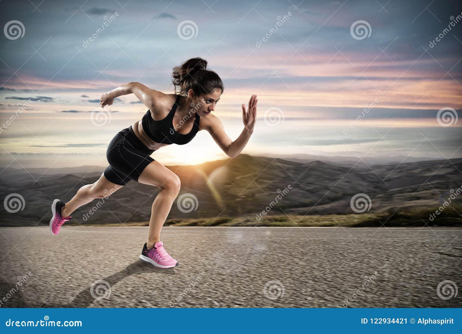 La femme sportive court sur la rue pendant le coucher du soleil