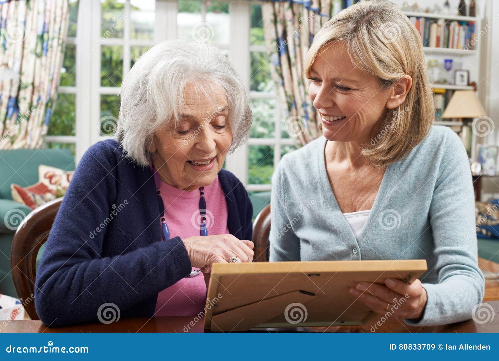 La femme supérieure regarde la photo dans le cadre avec le voisin féminin mûr