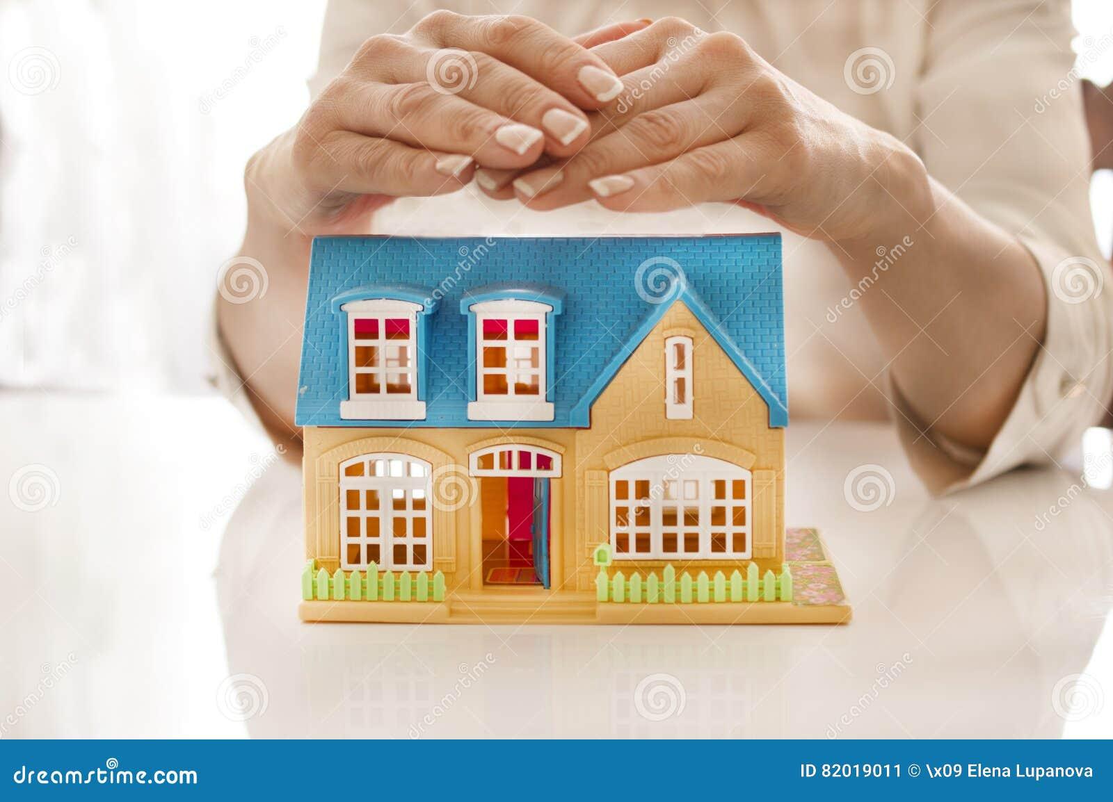 la femme tenant son protecteur remet une maison photo. Black Bedroom Furniture Sets. Home Design Ideas