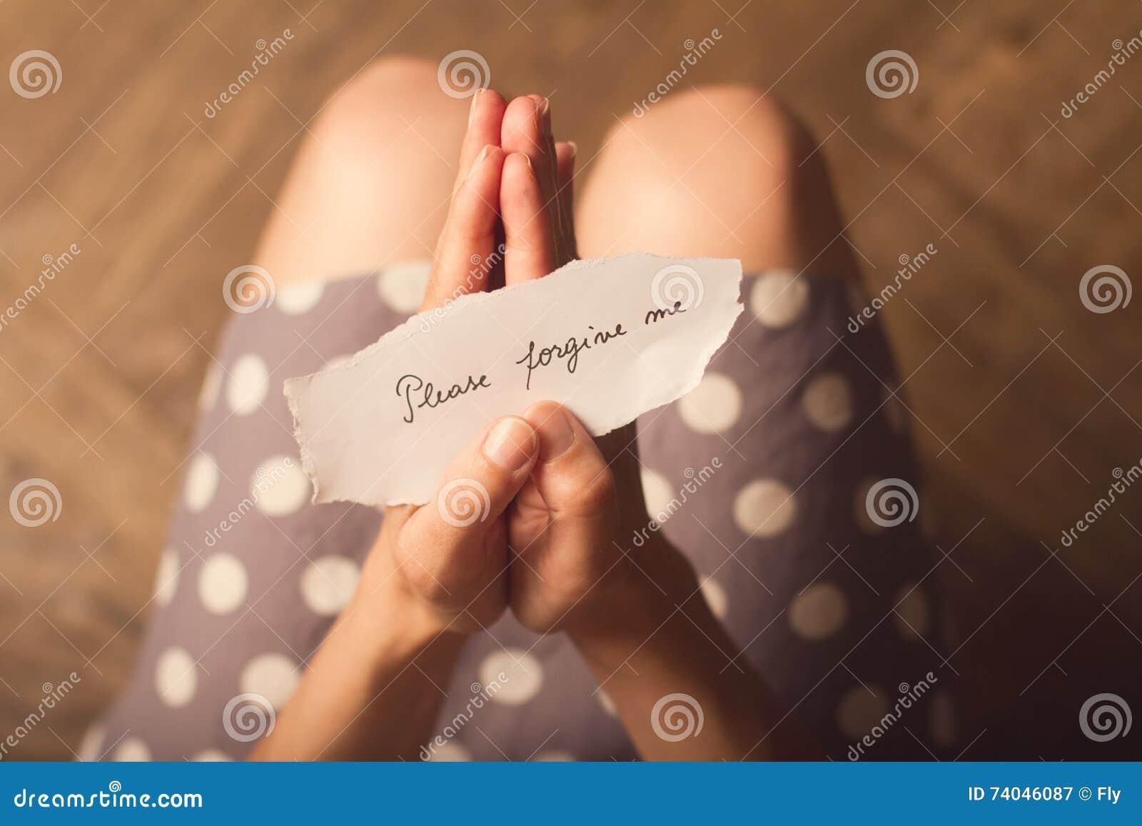 La femme tenant une note de papier avec le texte svp me pardonnent