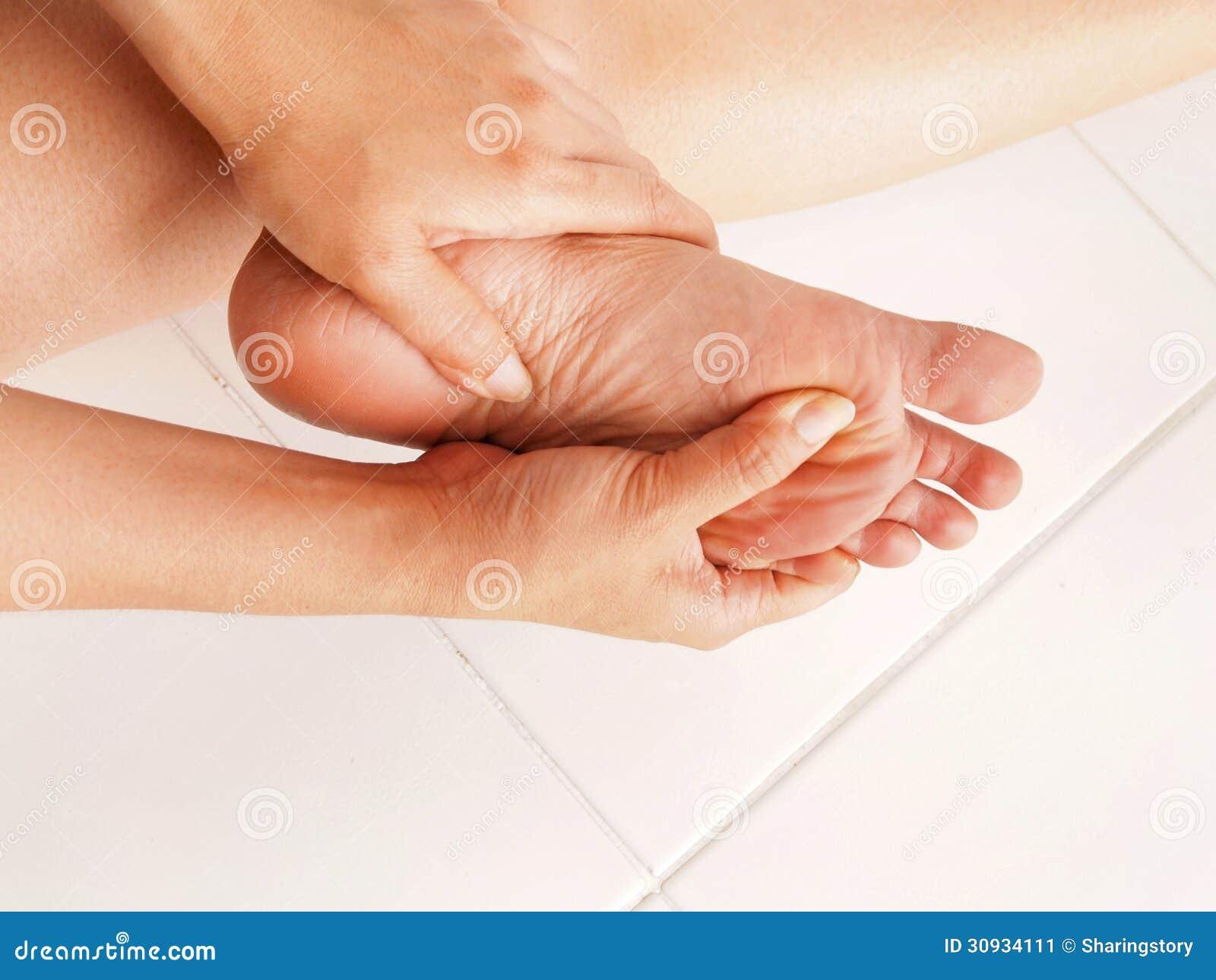 La femme vérifie son pied douloureux
