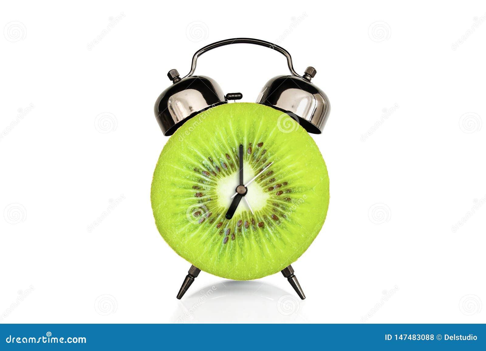 La fetta del kiwi sulla sveglia, isolata su fondo bianco, frutta e vitamine ? a dieta il concetto di nutrizione
