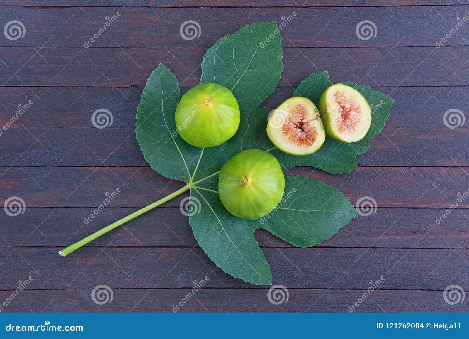 La figue mûre porte des fruits avec la feuille verte du figuier sur le fond foncé Configuration plate