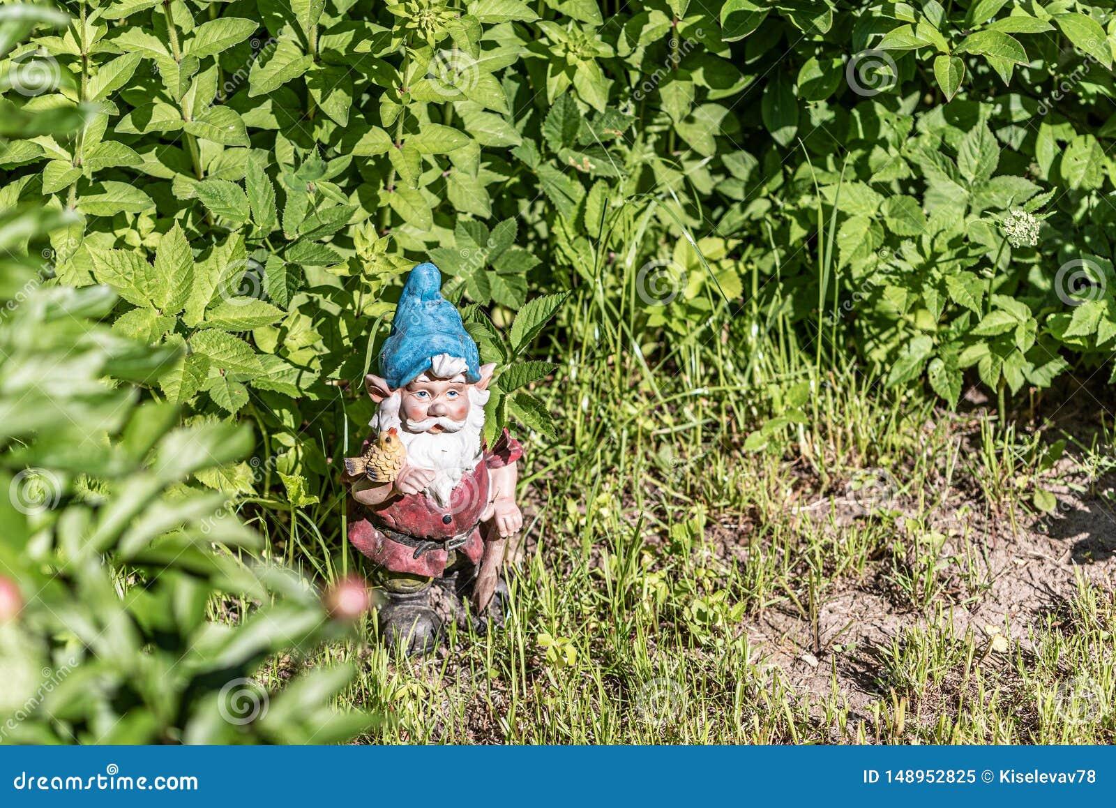 La figura di uno gnomo del giardino nell erba verde Copi lo spazio Fuoco selettivo