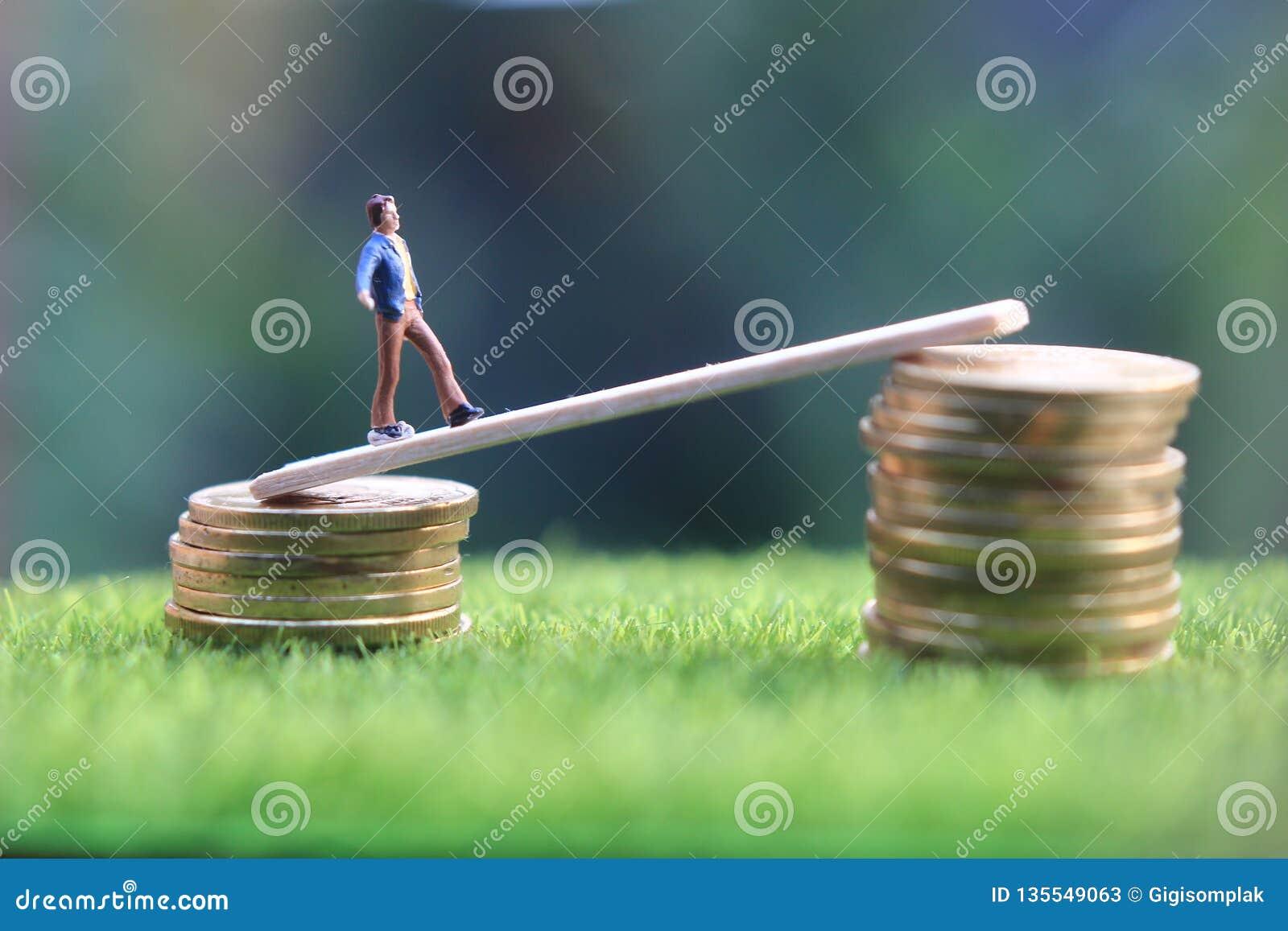 La figura miniatura bussinesman joven guarda el intentar conseguir una renta más alta que camina en la pila de moneda en la hierb