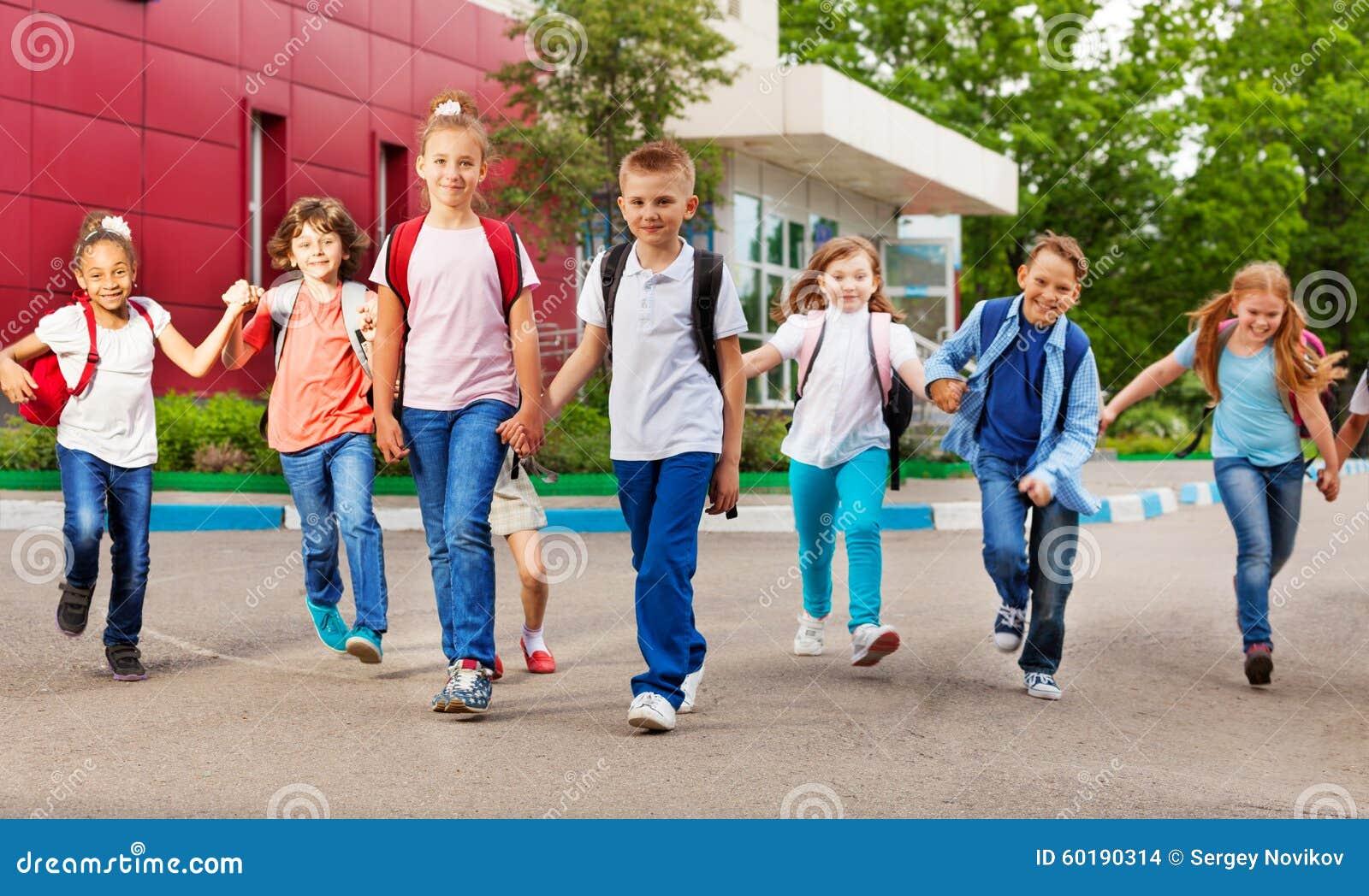 La fila dei bambini felici con le borse si avvicina all edificio scolastico