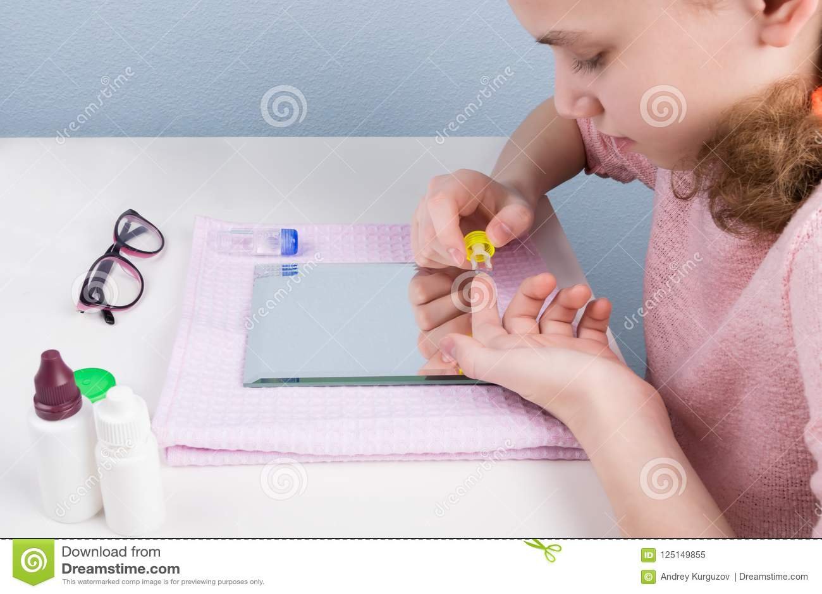 La fille à la table dispose à utiliser des verres de contact devant le miroir