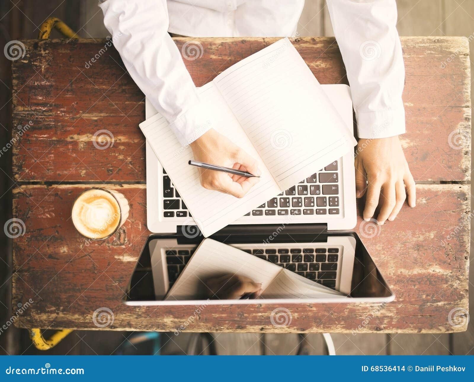 La fille écrit dans un carnet sur un bureau en bois avec une tasse