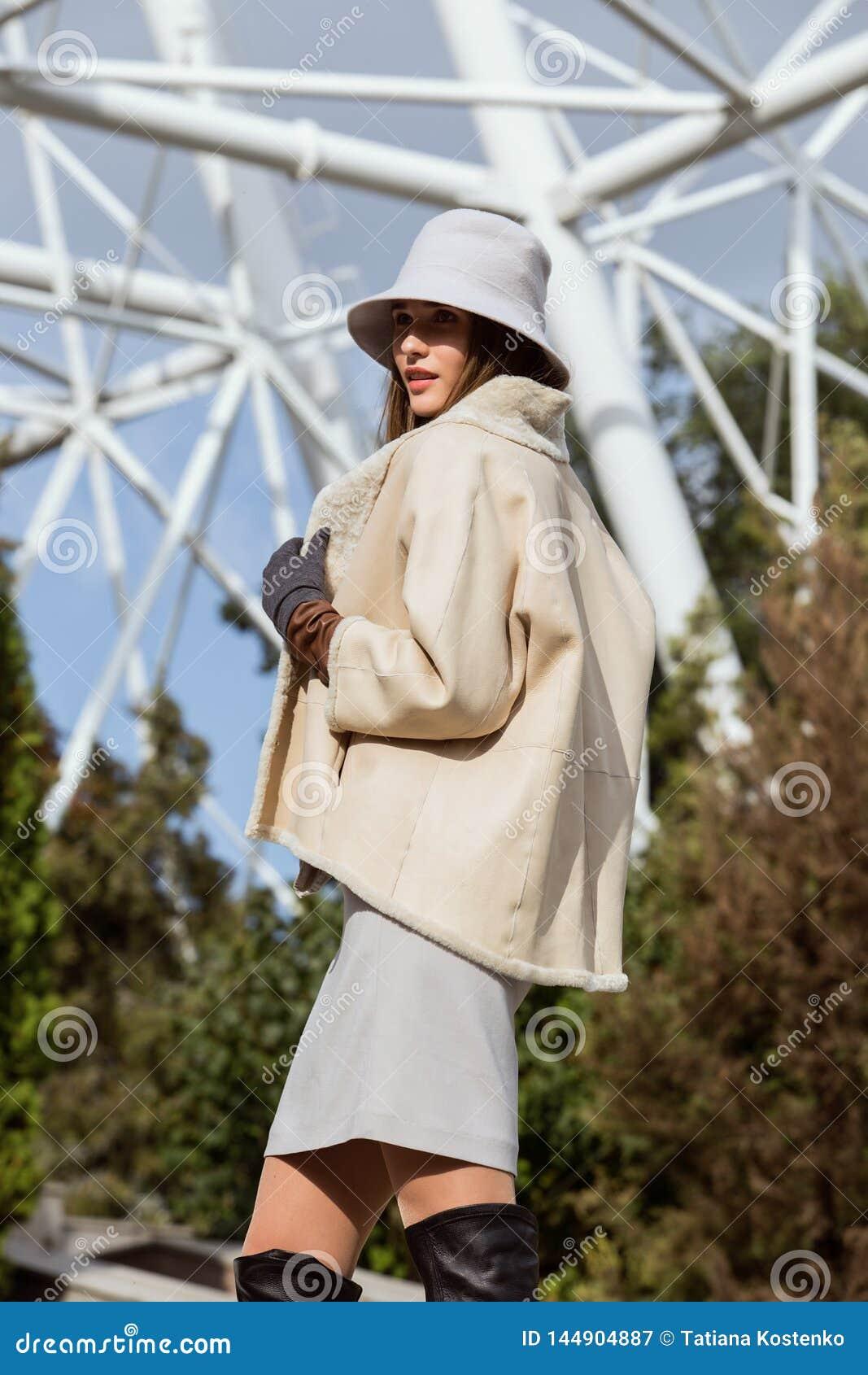 La fille élégante de brune habillée dans le manteau de peau de mouton court beige, les gants gris et le petit chapeau pose l e