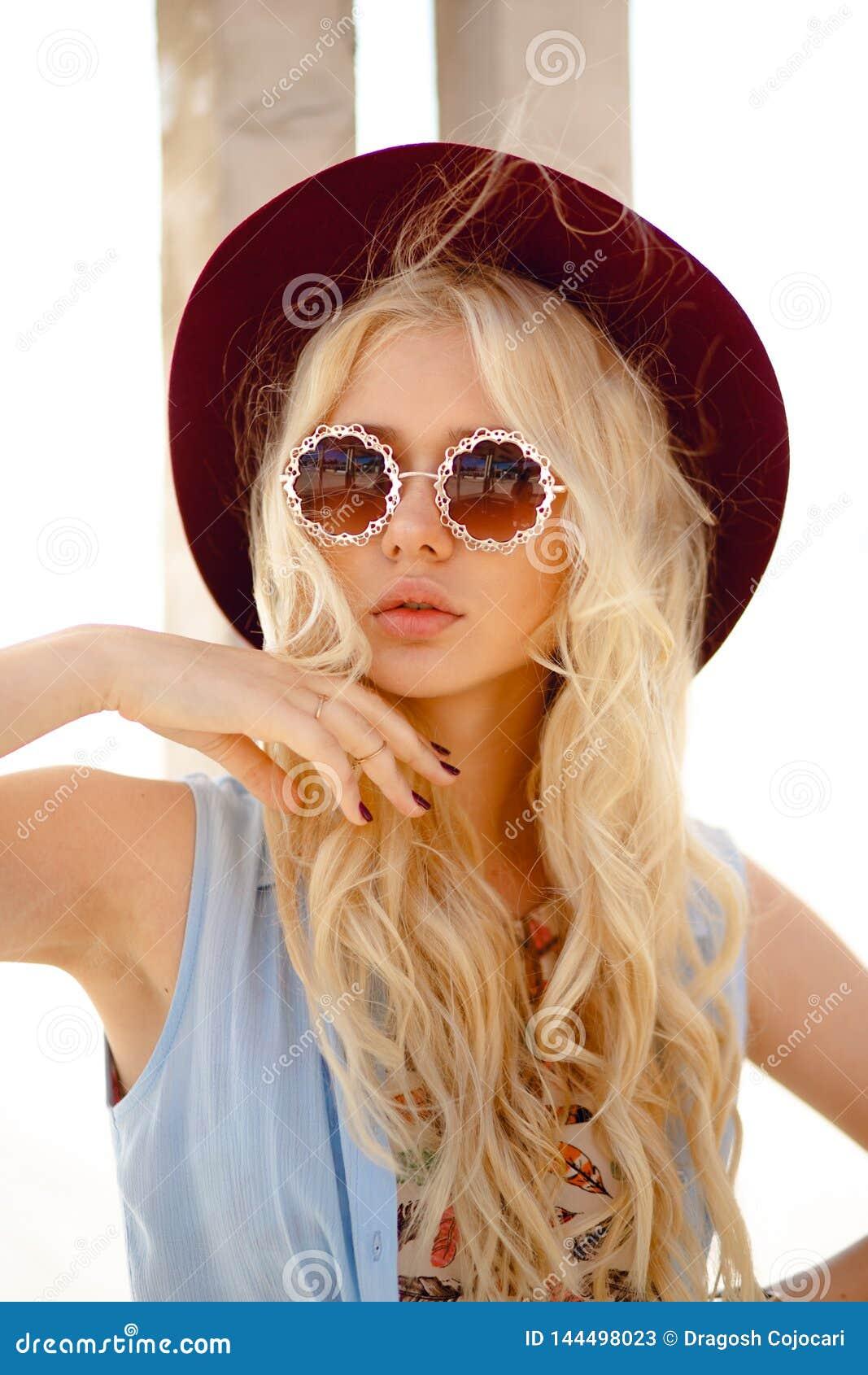 La fille élégante pose sur l endroit de soleil, portant dans un chapeau et des lunettes de soleil florales de rond, contact sensu