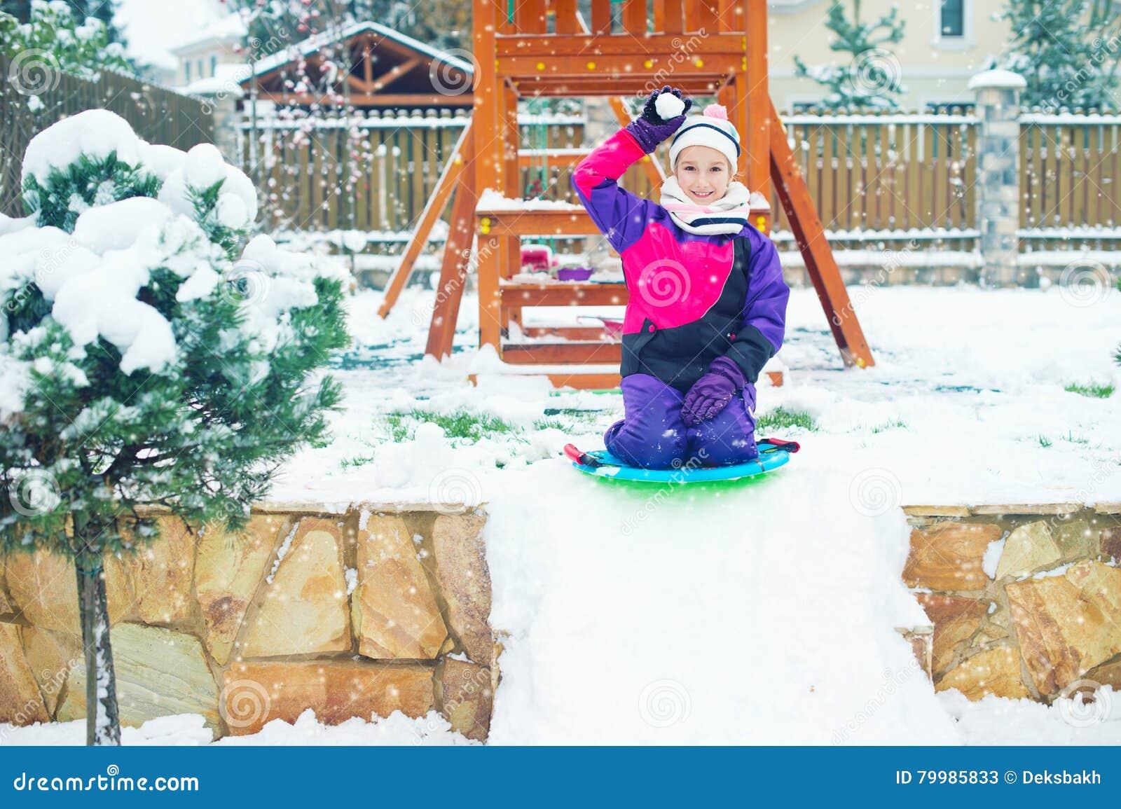 La fille émotive d âge scolaire joue le combat de boule de neige dans la cour d hiver