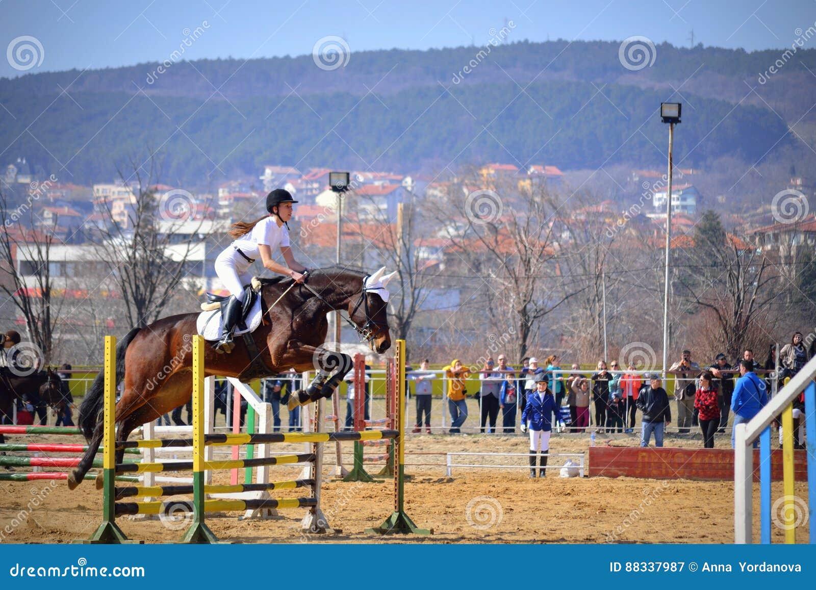 Cheval sautant de fille de l adolescence équestre au-dessus des rails  pendant la concurrence équestre pour les cavaliers juniors et jeunes à  l occasion des ... 6ab22e7c514