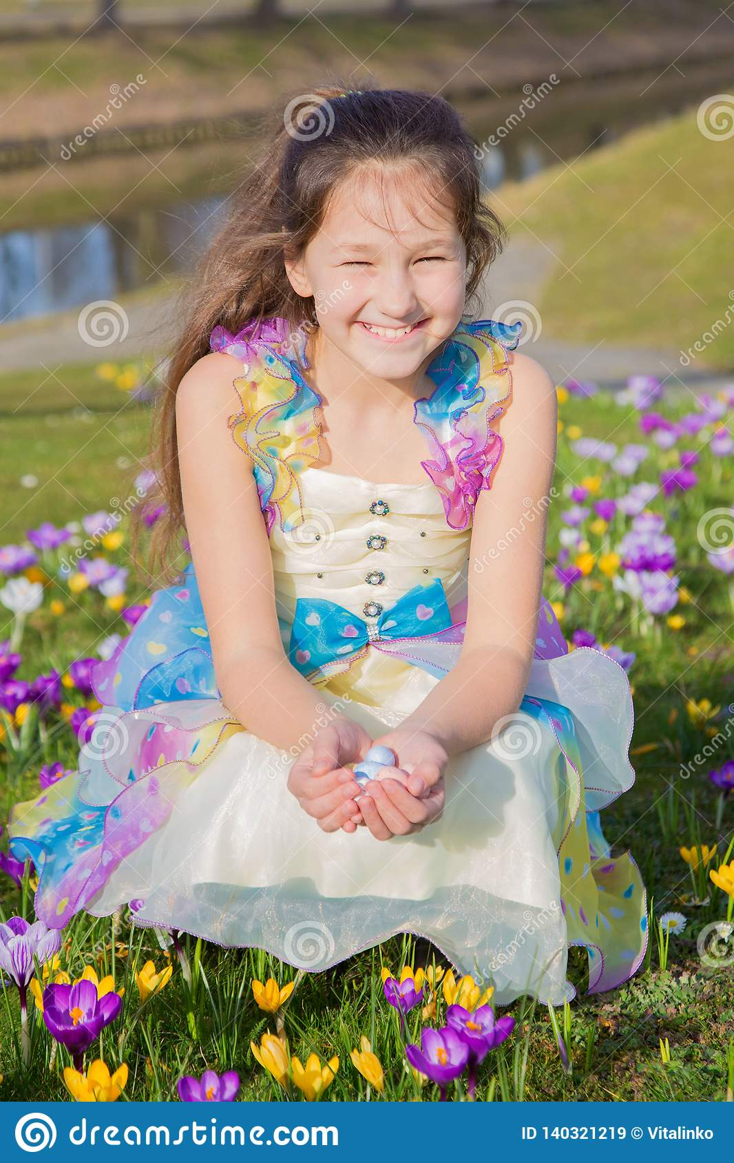 La fille adorable rassemble des oeufs de chocolat de Pâques parmi des fleurs