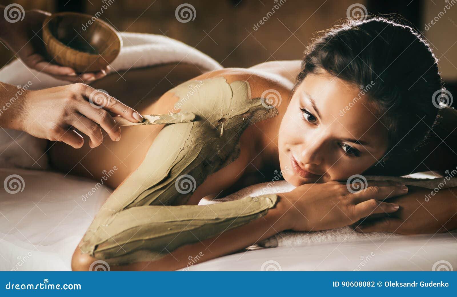 La fille apprécie le masque de corps de boue dans un salon de station thermale Foyer sur la main avec le bâton