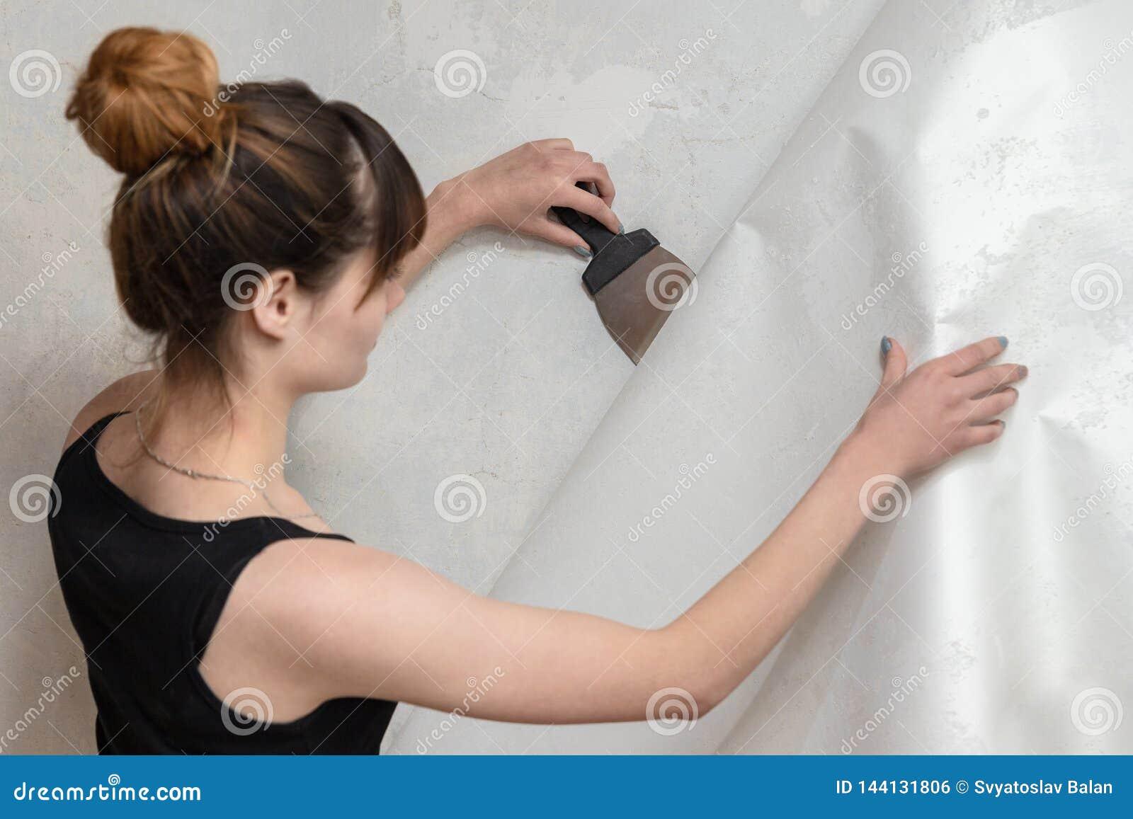 La fille arrache le vieux papier peint du mur en béton et tient une spatule