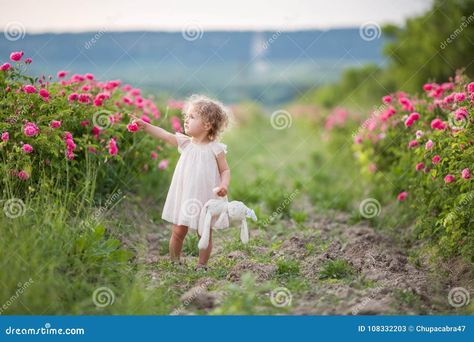 La fille assez boucl e d 39 enfant marche au printemps jardin - Fleurs roses de printemps ...