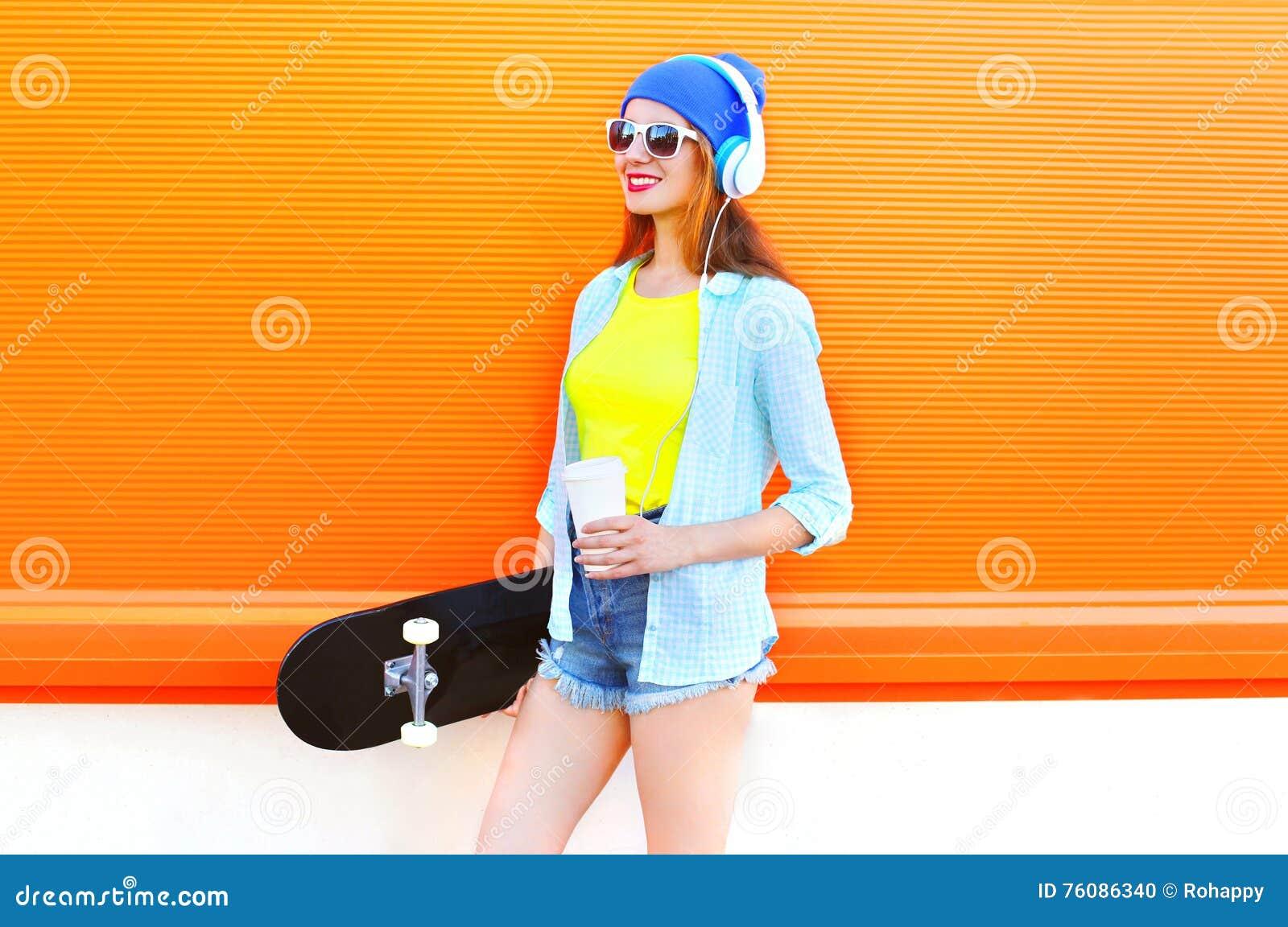 La fille assez fraîche de mode avec la tasse de café de planche à roulettes écoute la musique au-dessus de l orange colorée