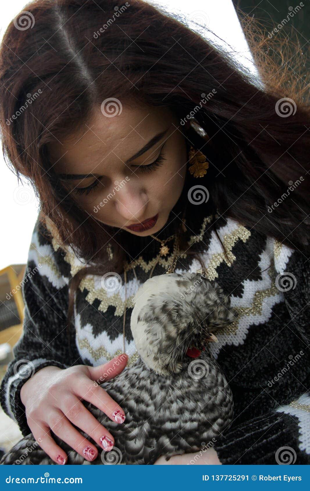 La fille aux cheveux longs à une ferme embrasse un poulet pelucheux