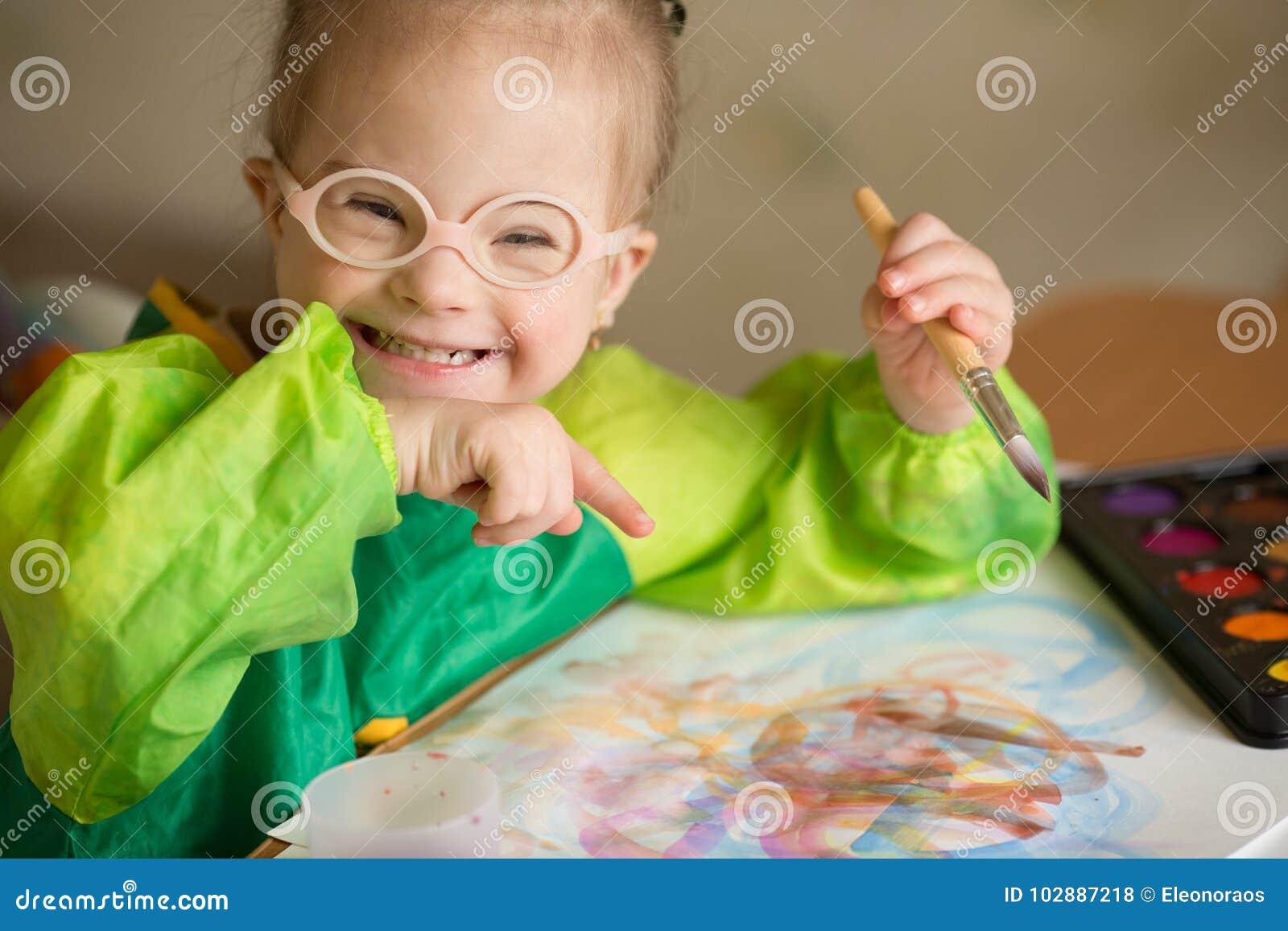 La fille avec la trisomie 21 dessine des peintures
