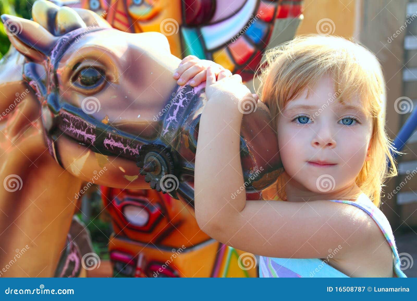 La fille blonde avec le cheval de champ de foire apprécient en stationnement