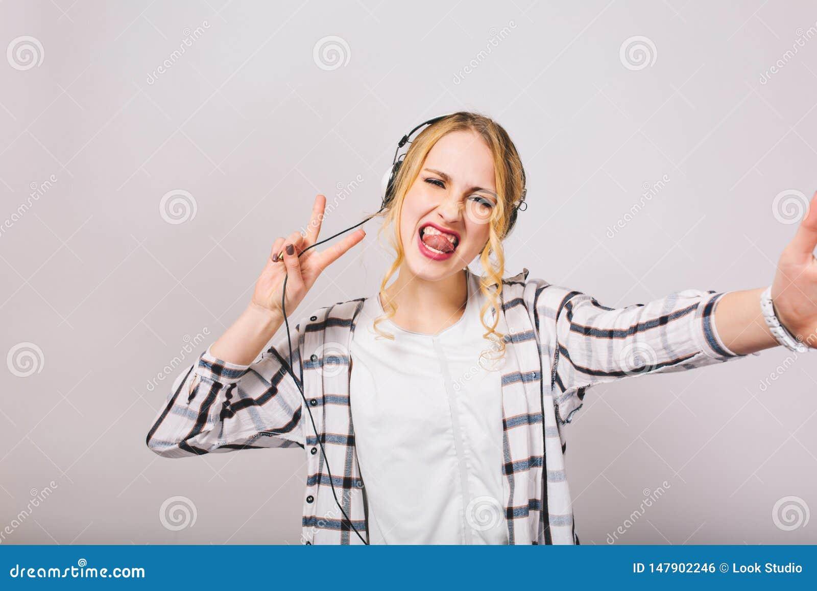La fille blonde dans des écouteurs avec la langue collant apprécie la musique et dupe autour de la danse sur le fond blanc