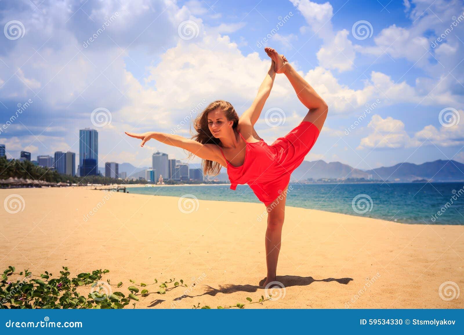 la fille blonde en rouge se tient dans l u0026 39  u00e9chelle gymnastique de jambe de position sur le sable
