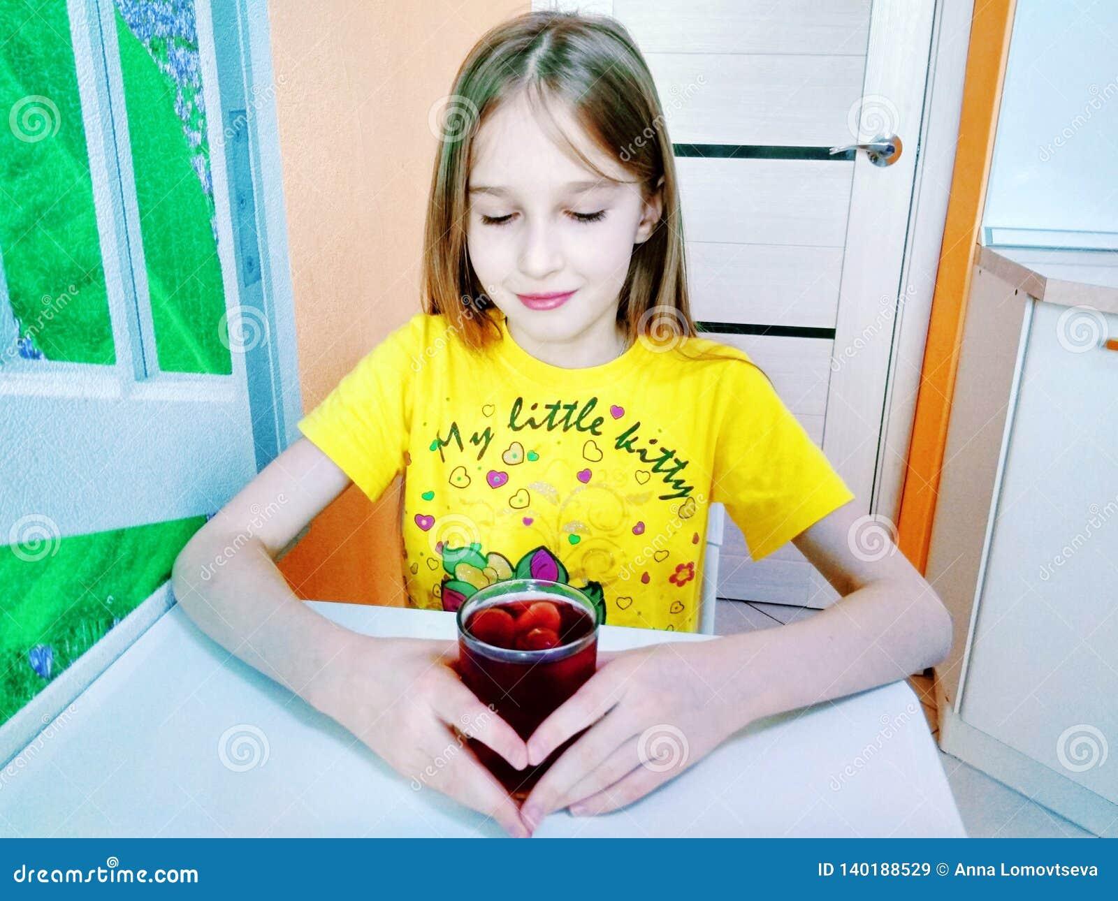 La fille boit l eau avec des morceaux de glace de fruit