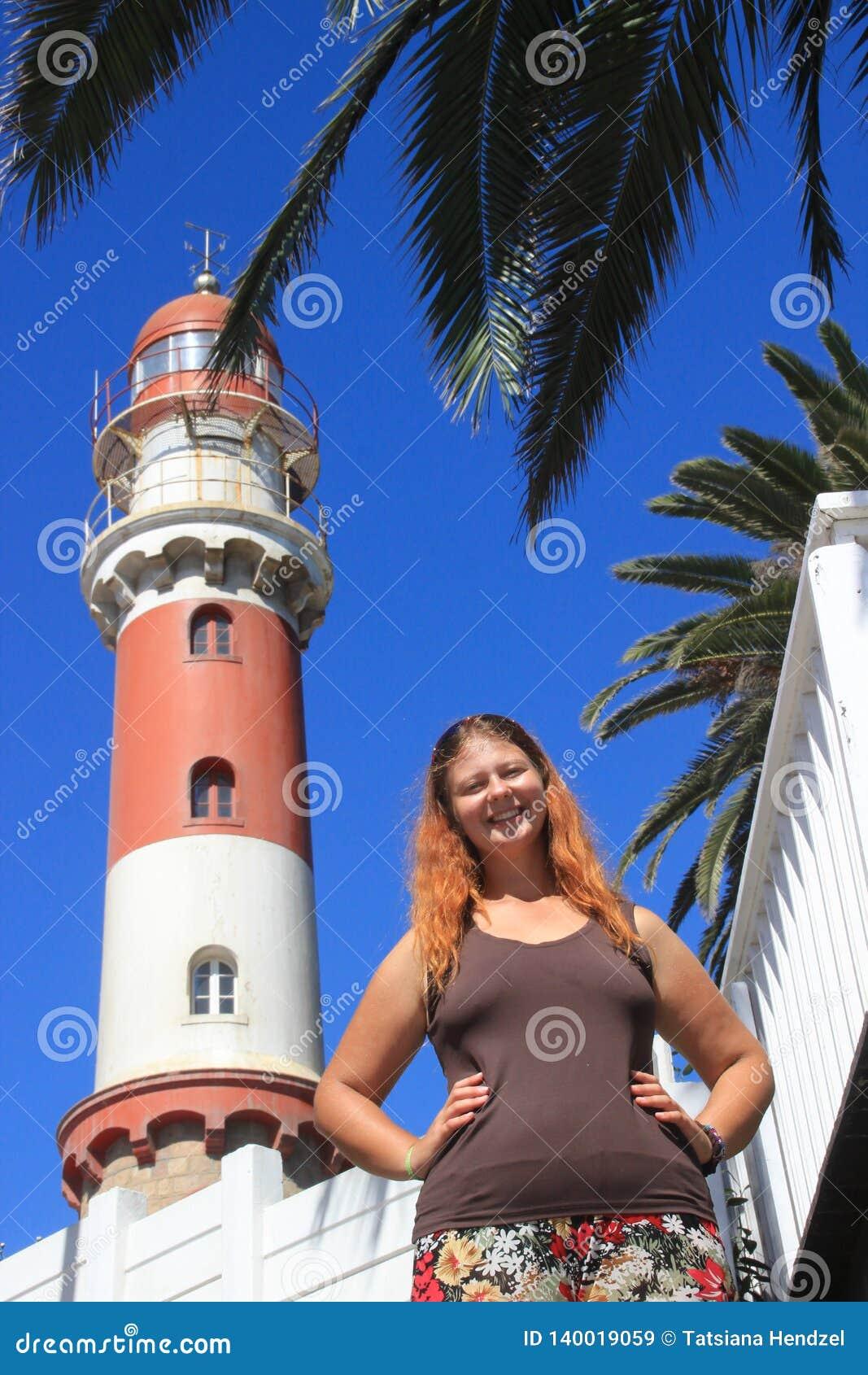La fille caucasienne blanche heureuse rousse se tient à côté des phares en Swakopmund Namibia et gaiement sourires