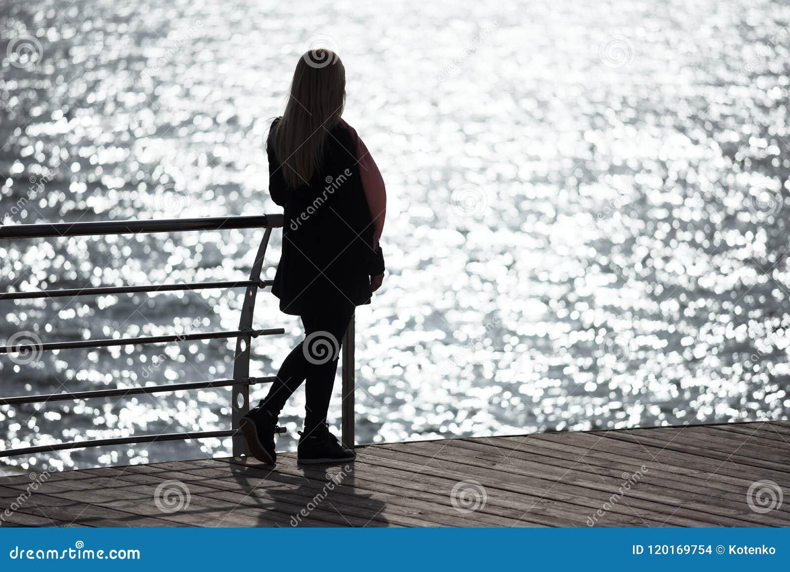 La fille contemplent l éclat de lumière du soleil en mer