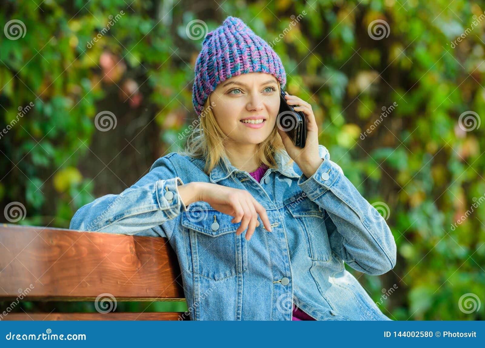 La fille a la conversation de téléphone portable dans le parc détendez sur le banc dans srpring Ami de attente Partager des nouve