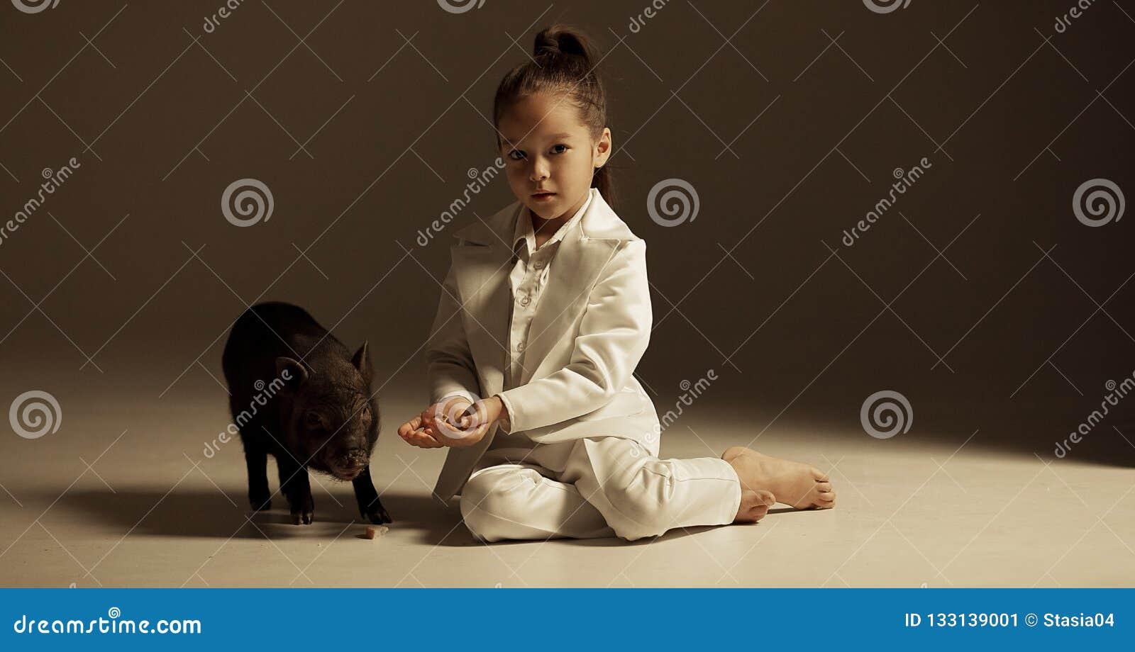 La fille d enfant est reposante et alimentante le porcelet vietnamien noir