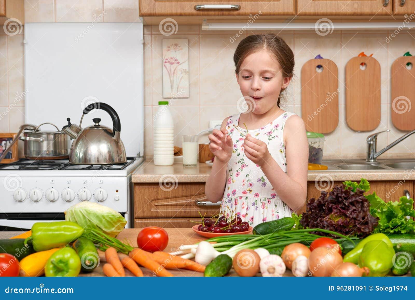 La fille d enfant mangent les cerises, fruits et légumes dans la cuisine à la maison intérieure, concept sain de nourriture