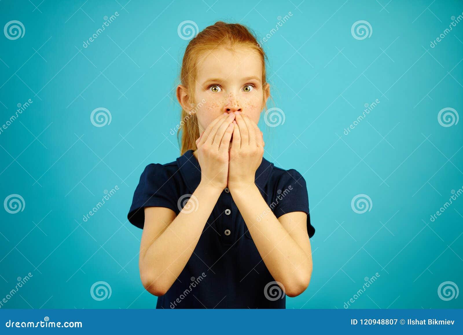 La fille d une chevelure rouge avec de grands yeux de la crainte a couvert la bouche de mains sur le fond bleu
