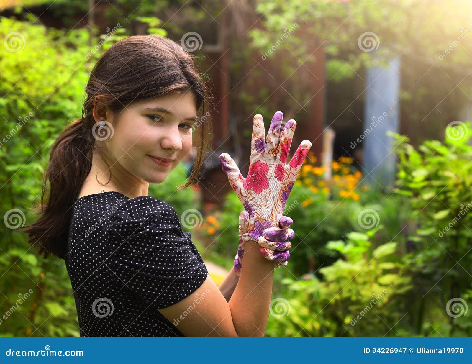 La fille dans des gants de robe et de jardin de point de polka l été verdissent le fond de pays