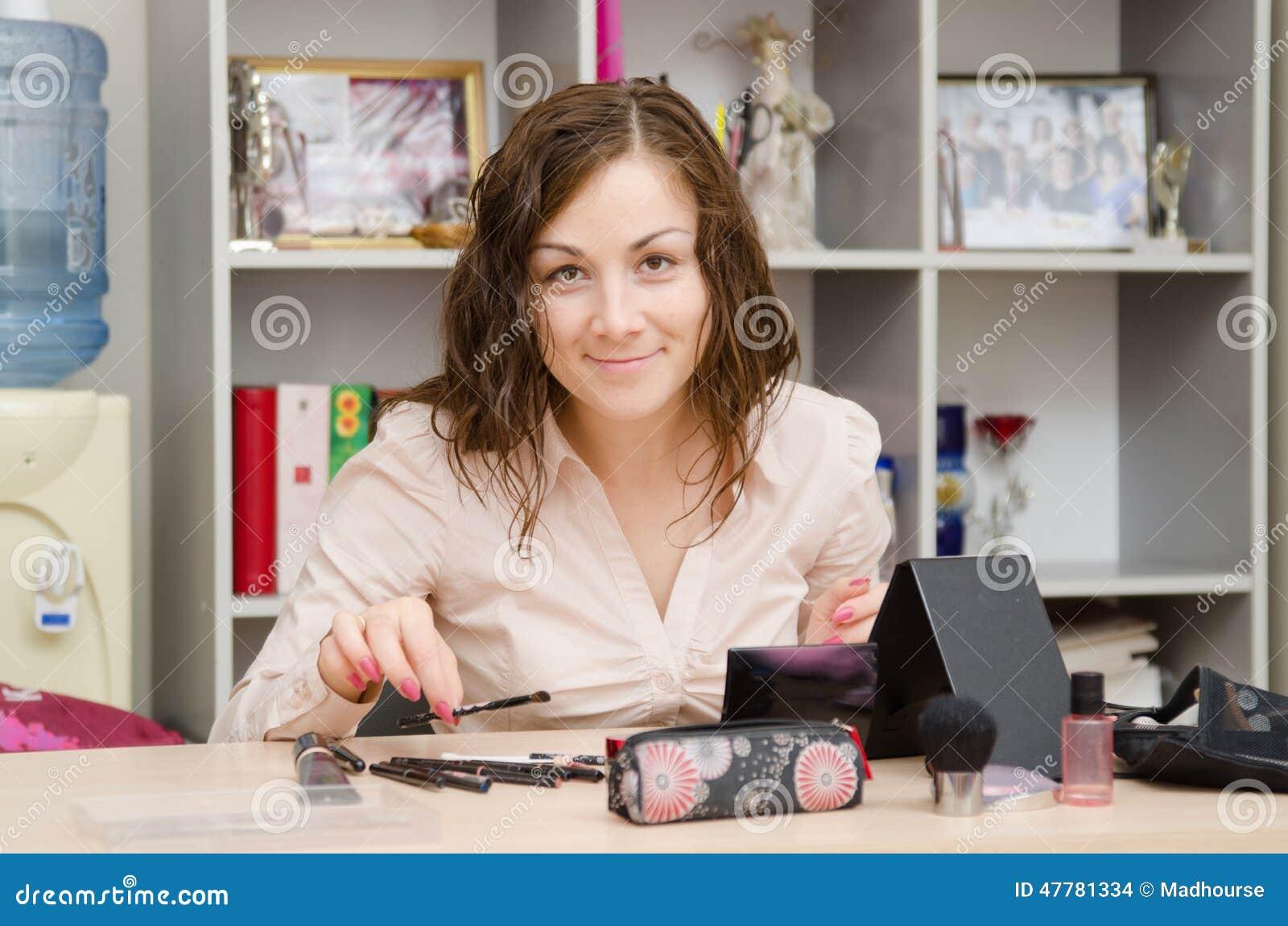 La fille dans le bureau sélectionne la brosse appropriée pour le