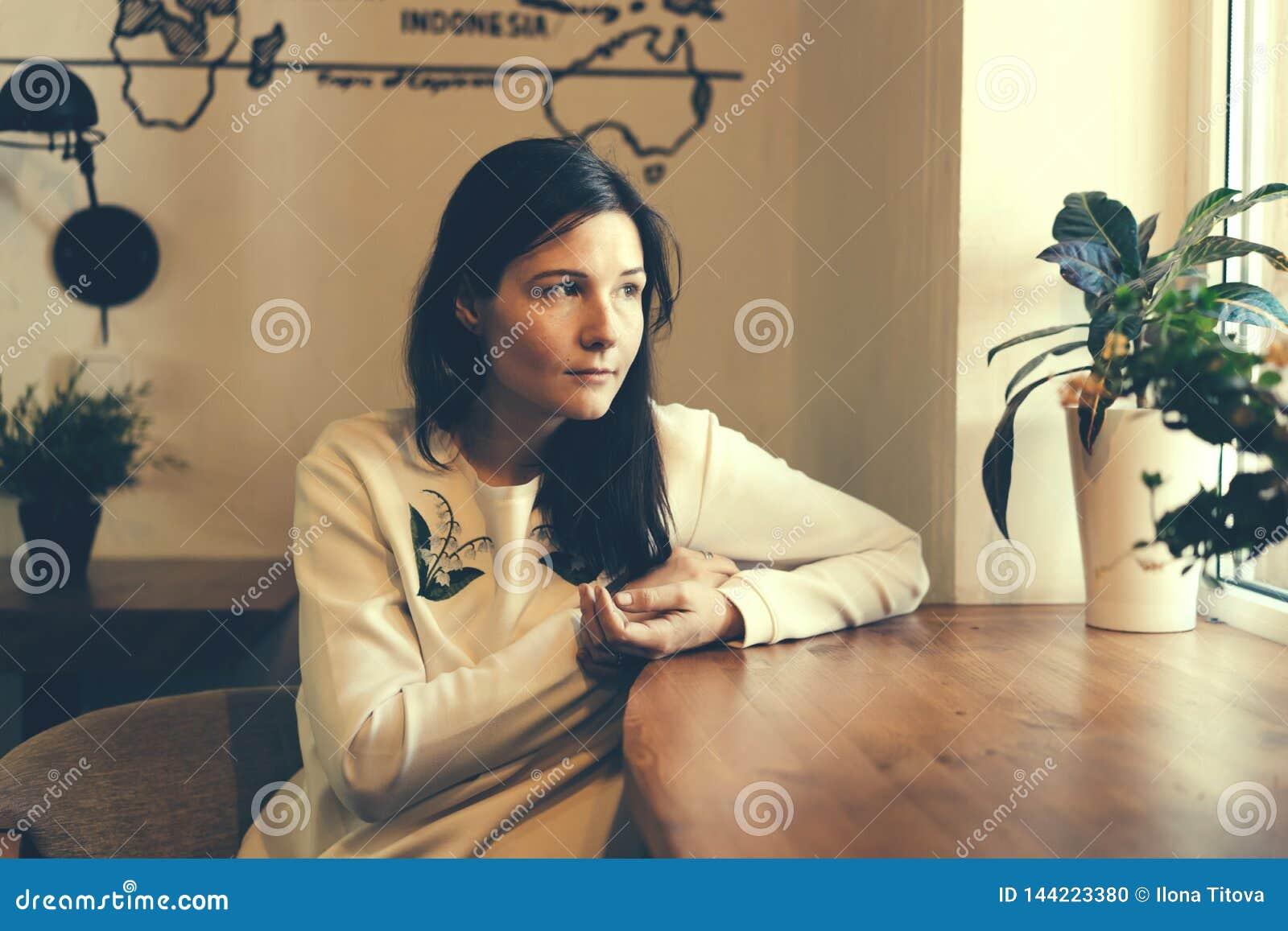 La fille dans le café par la fenêtre