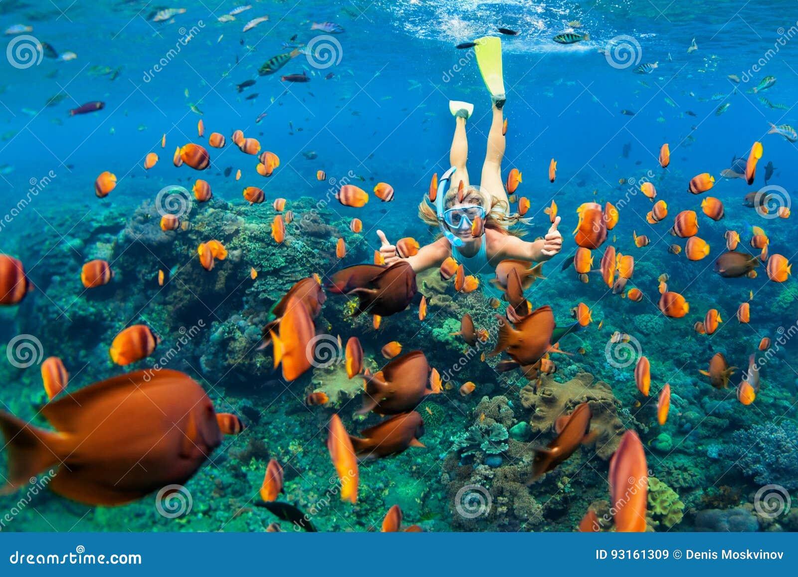 La fille dans le piqué naviguant au schnorchel de masque sous l eau avec le récif coralien pêche