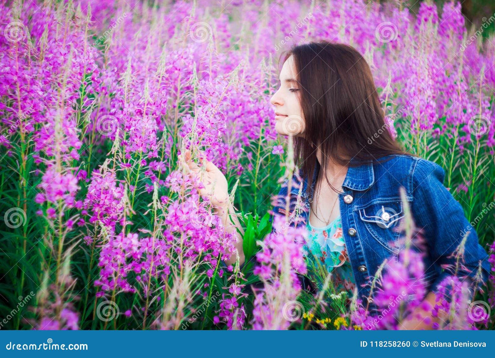 La fille dans le profil sur un fond des prés pourpres de fleur avec un sourire regardant les fleurs