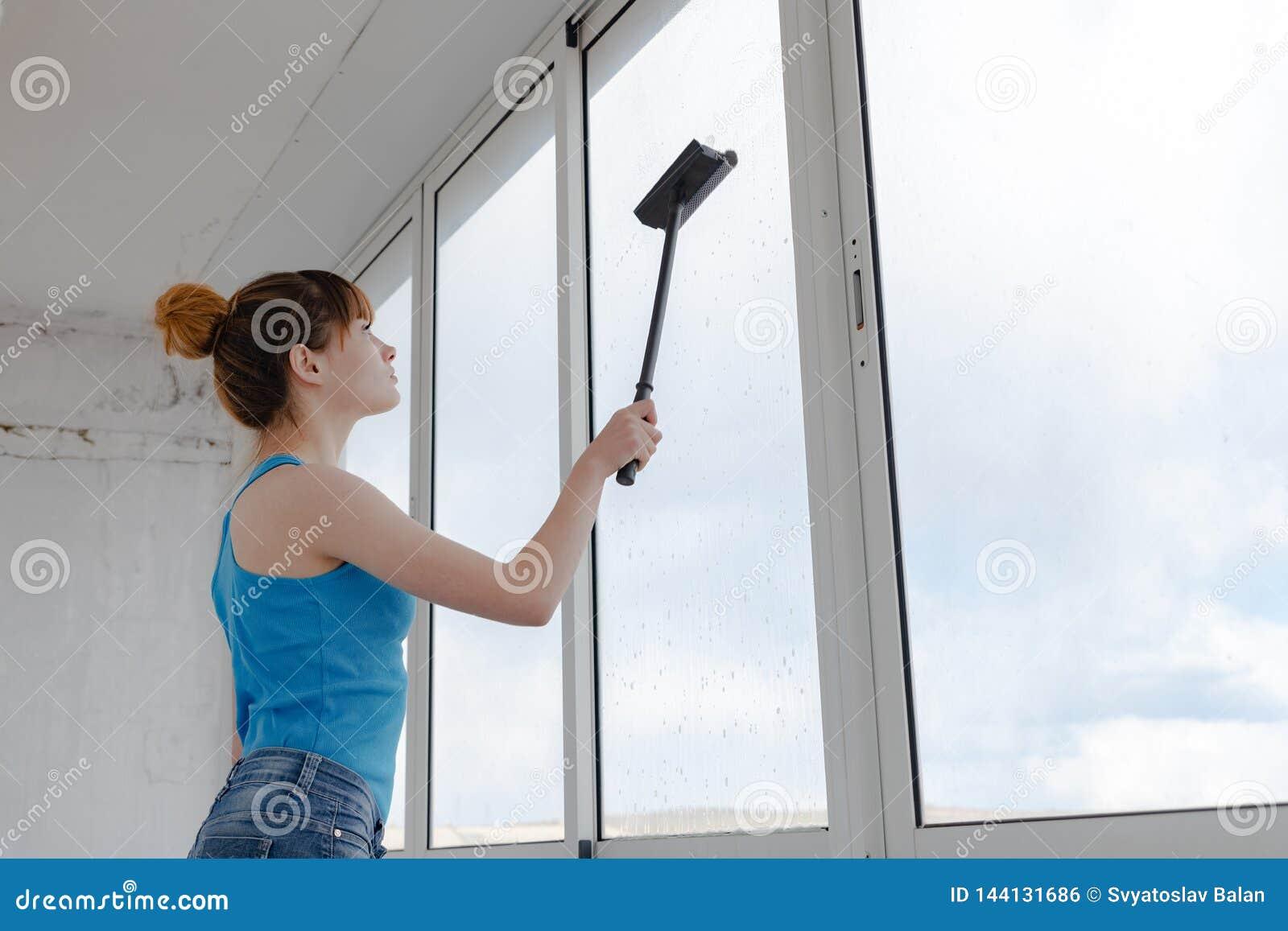 La fille dans le T-shirt et les shorts bleus de turquoise lave la fenêtre