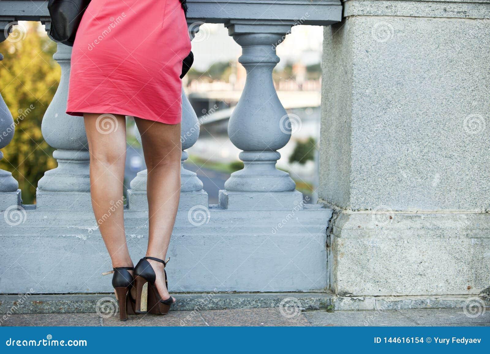 La fille dans la robe rouge dans la perspective de la balustrade