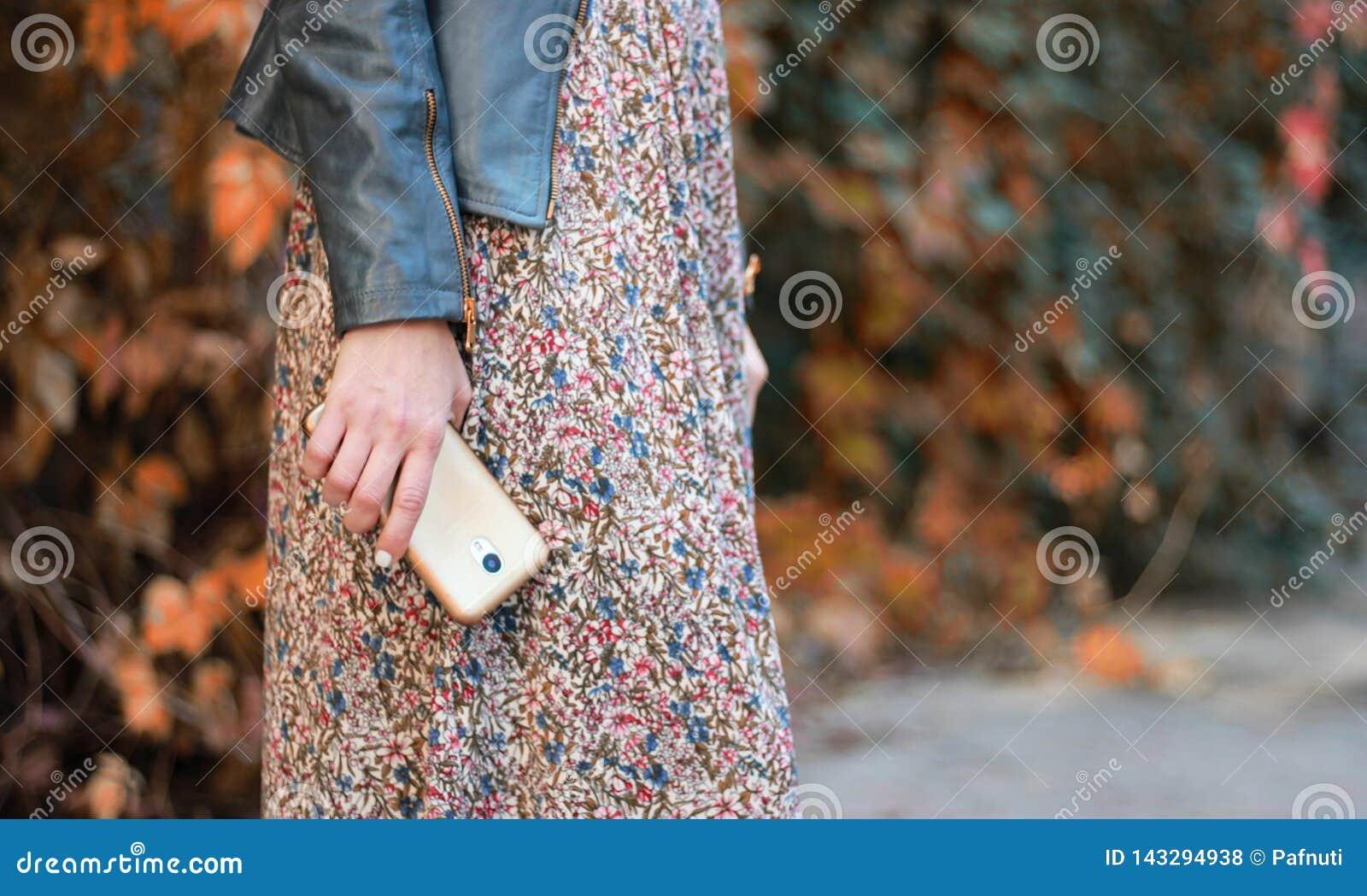 La fille dans la robe tient le téléphone
