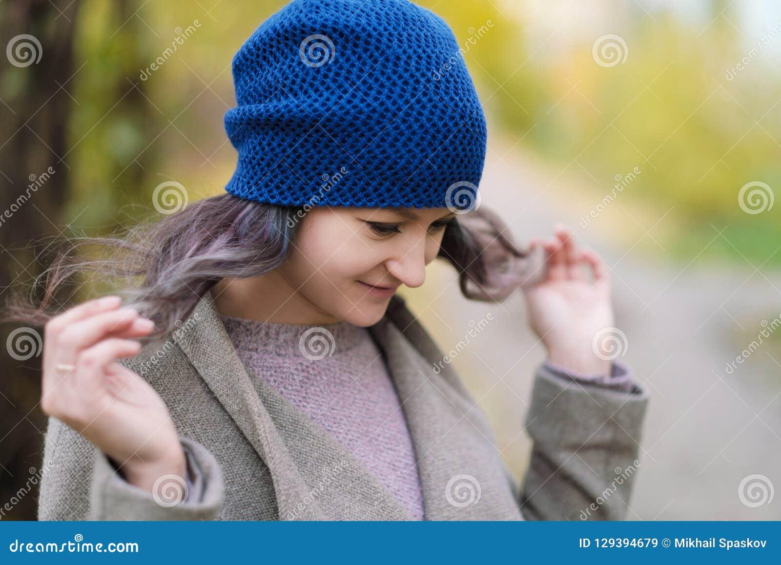 La fille dans un manteau et un chapeau bleu sur un fond des arbres d automne et des feuilles d érable